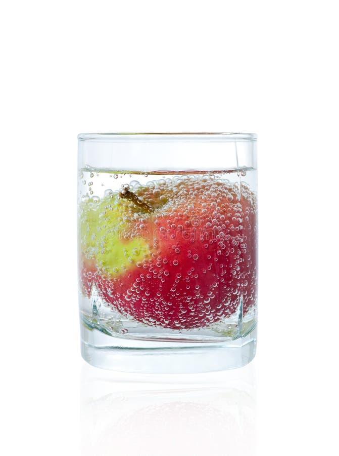 Apple no vidro da água mineral foto de stock royalty free