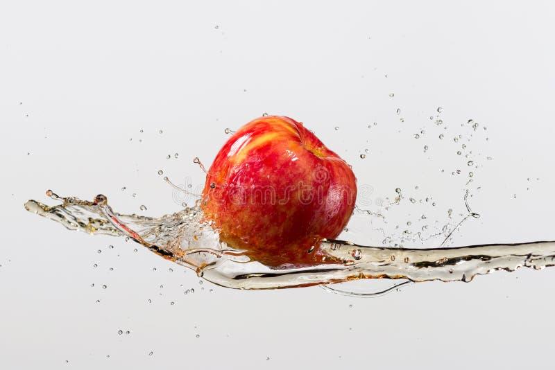 Apple och färgstänk av fruktsaft som isoleras på grå bakgrund royaltyfria bilder