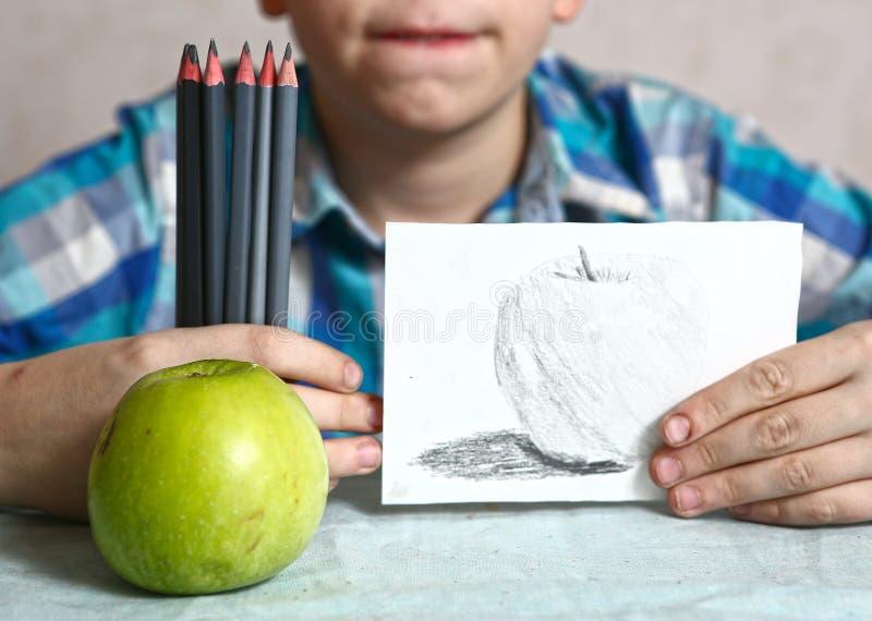 Apple och teckning i ungehänder royaltyfri fotografi