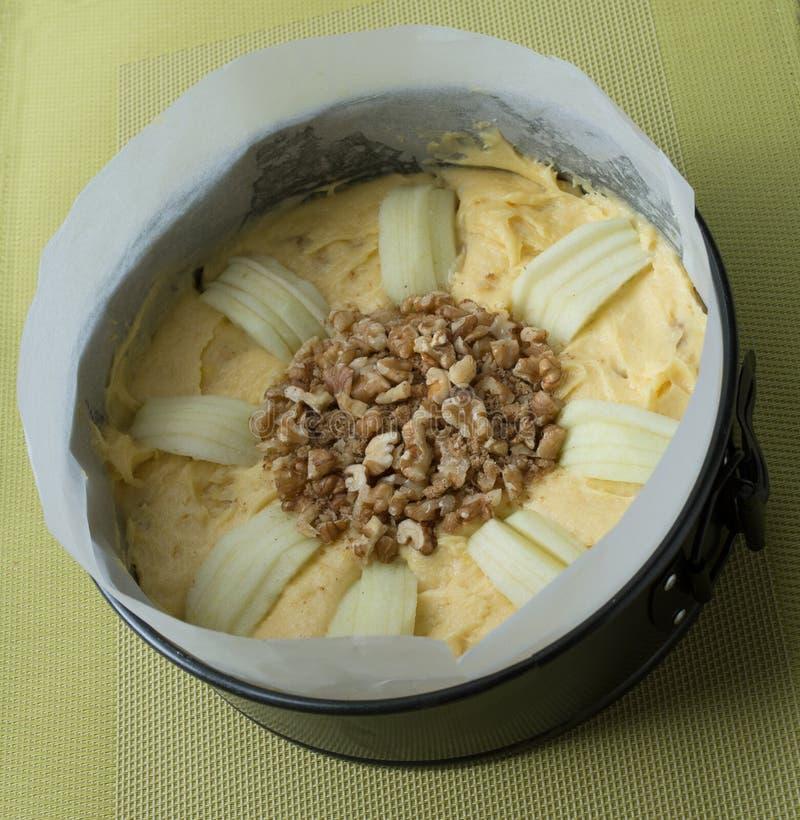 Apple och valnötkakablandning i papper fodrad stekhet panna royaltyfri foto
