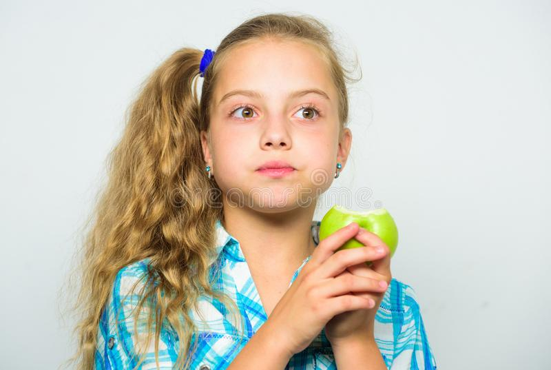 Apple om dagen håller doktorn bort Bra näring är nödvändig till goda hälsor Ungeflickan äter grön äpplefrukt näringsrikt arkivfoto