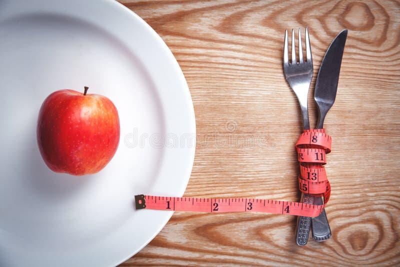 Apple op een witte plaat Meetlint met vork en mes Dieet, gezondheid royalty-vrije stock foto's