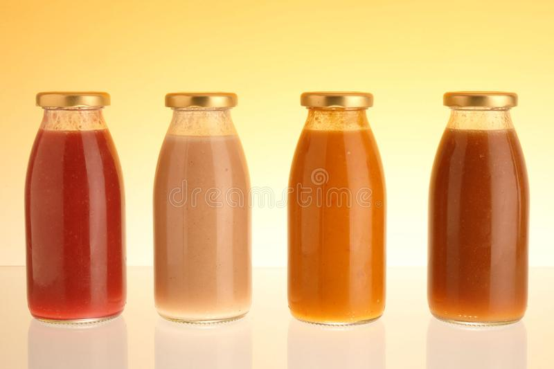 Apple, peach, carrot and plum juice in a glass bottle stock image