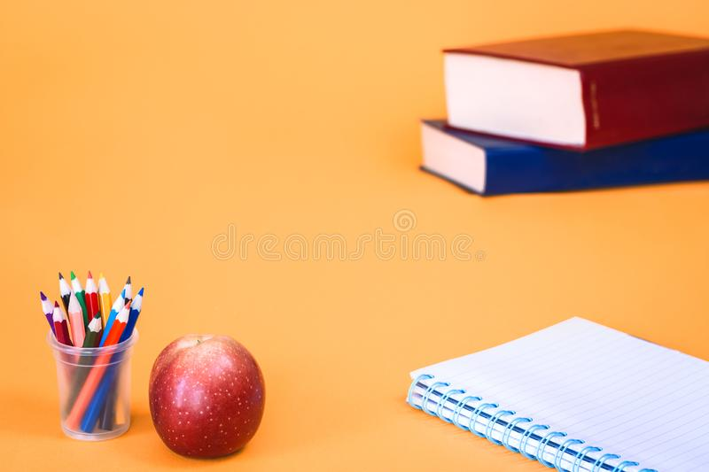 Apple with pencils and school books on orange background royalty free stock photography