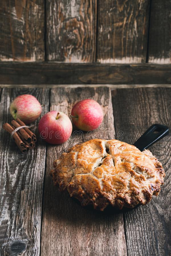 Apple pie in cast iron skillet, traditional Thanksgiving dessert. Autumn cozy dish on rural wooden table, close up, selective focus royalty free stock images