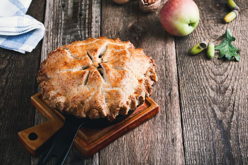 Apple pie in cast iron skillet, traditional Thanksgiving dessert. Autumn cozy dish on rural wooden table, close up, selective focus stock photography