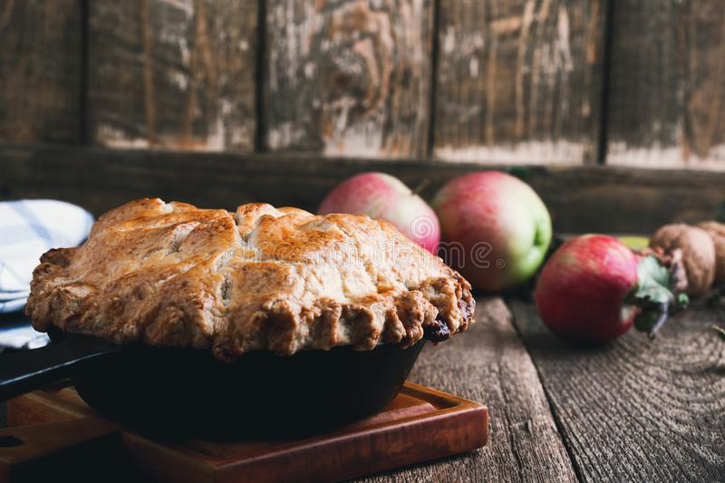 Apple pie in cast iron skillet, traditional Thanksgiving dessert. Autumn cozy dish on rural wooden table, close up, selective focus stock photos