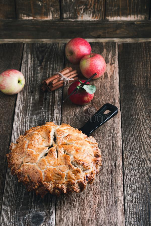 Apple pie in cast iron skillet, traditional Thanksgiving dessert. Autumn cozy dish on rural wooden table, close up, selective focus stock photo