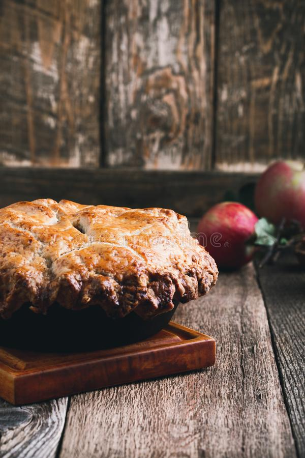 Apple pie in cast iron skillet, traditional Thanksgiving dessert. Autumn cozy dish on rural wooden table, close up, selective focus royalty free stock photography