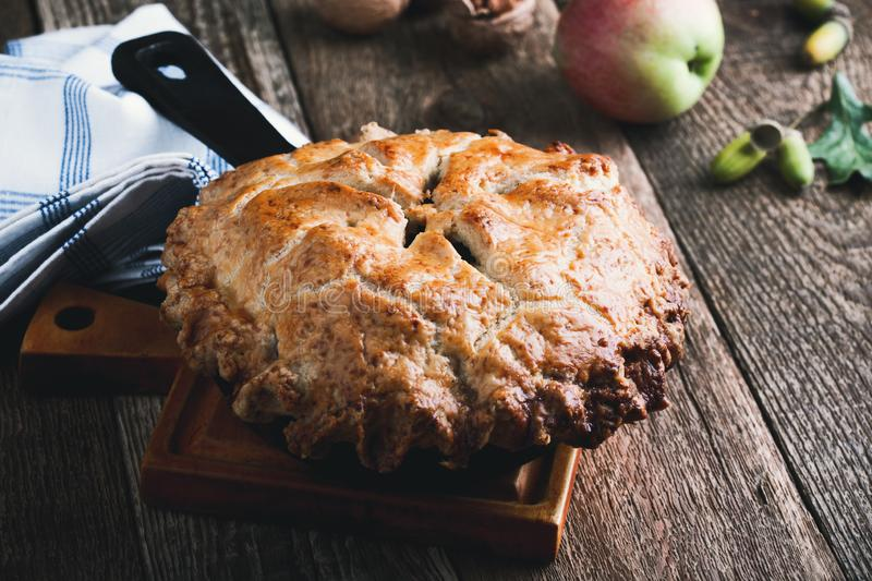 Apple pie in cast iron skillet, traditional Thanksgiving dessert. Autumn cozy dish on rural wooden table, close up, selective focus stock images