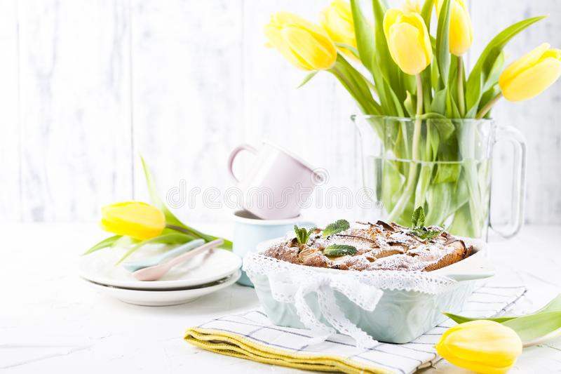 Apple pie in dishes on a white background and a bouquet of spring yellow tulips. Homemade pastries with fruit for a delicious stock image