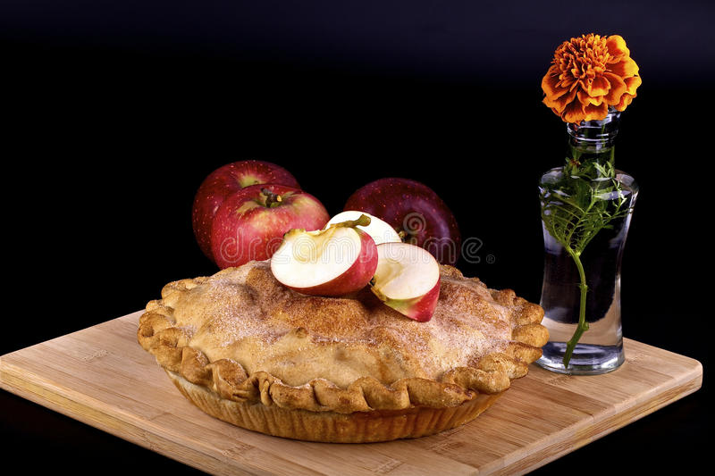 Apple pie. Homemade apple pie,red apples and flower in a vase on black background stock images