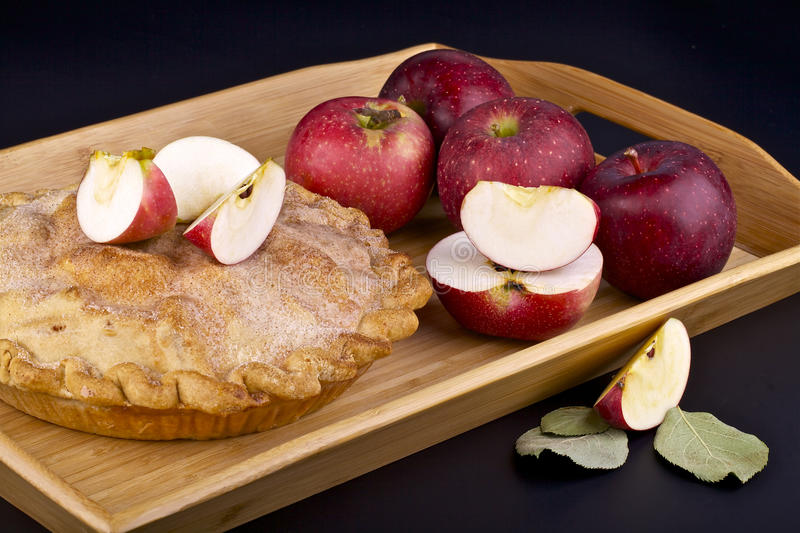 Apple pie. Homemade apple pie and red apples in wooden container on background stock photography