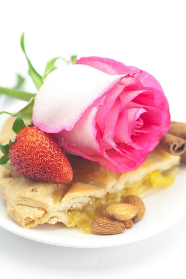 Apple pie, kanel, rosa ro, mandelar och jordgubbe arkivbilder