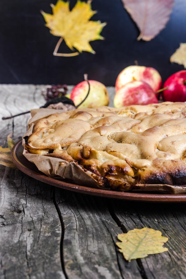 Apple-pie. Apple pie with red apples on a wooden board in the fall stock photography