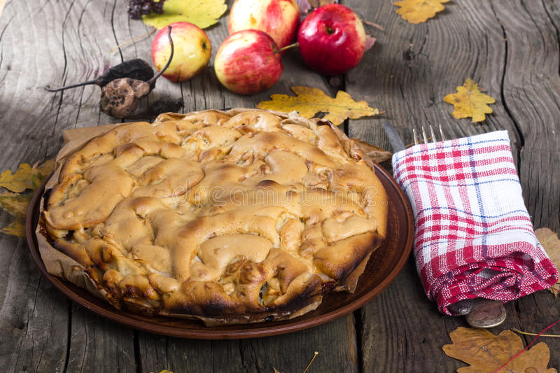Apple-pie. Apple pie with red apples on a wooden board in the fall royalty free stock image