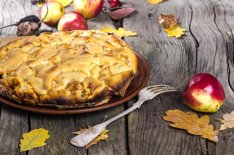 Apple-pie. Apple pie with red apples on a wooden board in the fall royalty free stock photography
