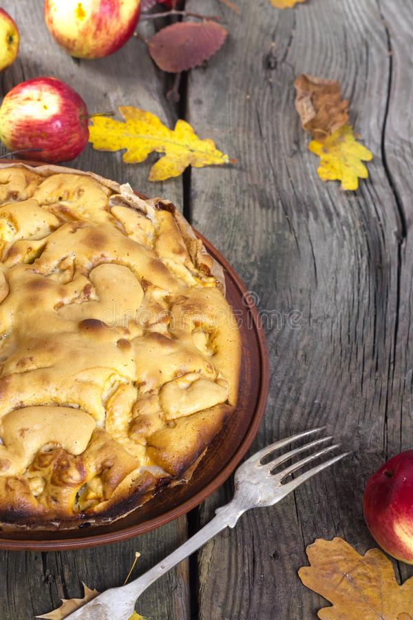Apple-pie. Apple pie with red apples on a wooden board in the fall royalty free stock photos