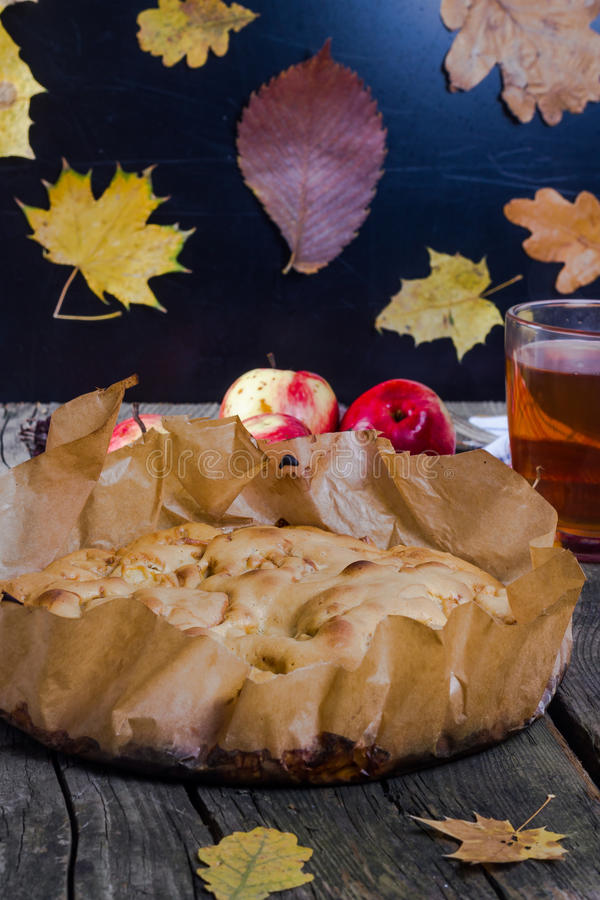 Apple-pie. Apple pie with red apples on a wooden board in the fall royalty free stock photo