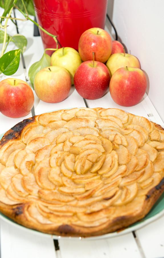 Apple pie with red and yellow apples in the background. An apple pie with red and yellow apples in the background royalty free stock photos
