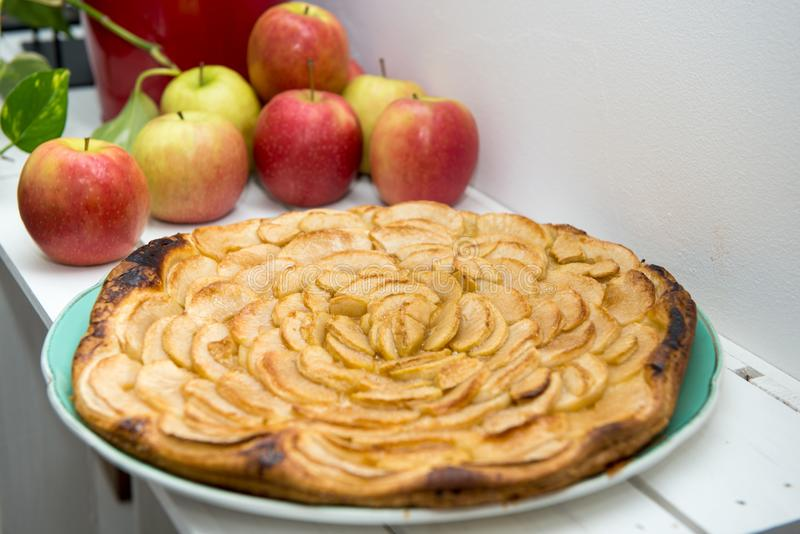 Apple pie with red and yellow apples in the background. An apple pie with red and yellow apples in the background stock photos