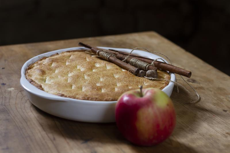 Apple pie in a white ceramic baking dish with cinnamon sticks royalty free stock photo