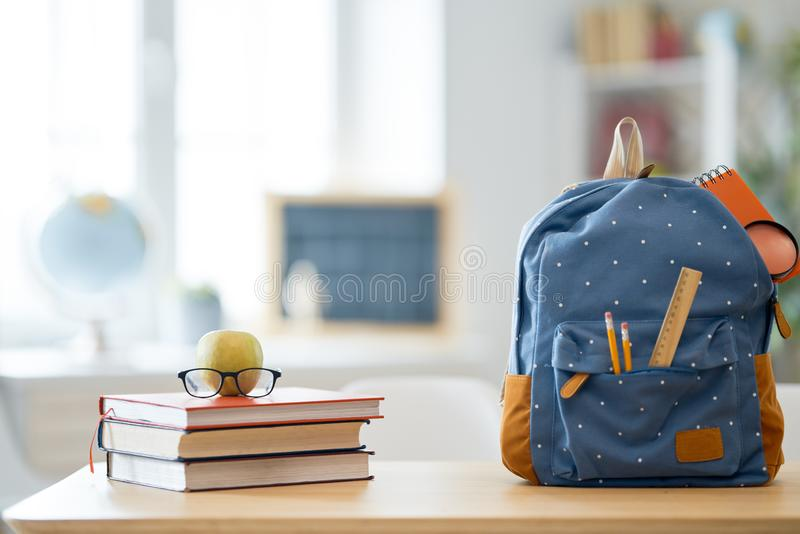 Apple, pile of books and backpack royalty free stock image