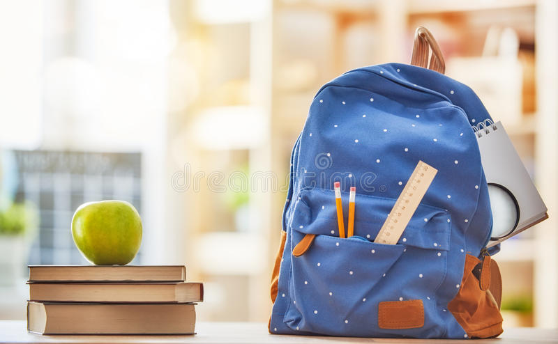 Apple, pile of books and backpack stock image