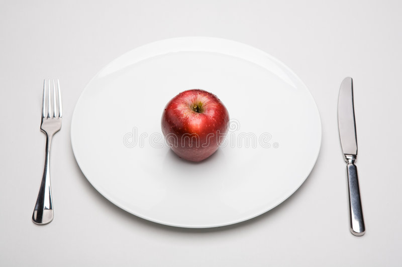 Apple on plate. Image of red apple on white plate with fork and knife near by stock photos