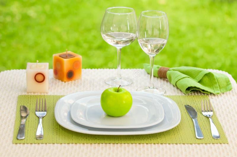 Apple platta med gaffeln och kniv mot äng. royaltyfri foto