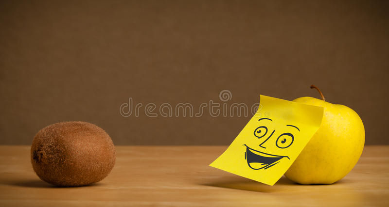 Apple with post-it note smiling at kiwi. Apple with sticky post-it note looking happy at kiwi stock images