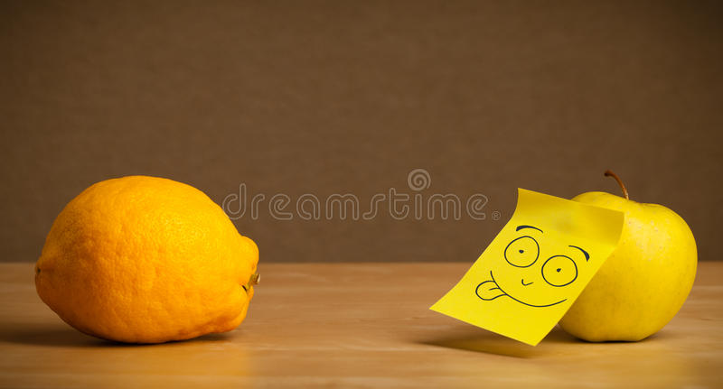 Apple with post-it note sticking out tongue to lemon. Apple with sticky post-it note showing tongue to lemon stock image