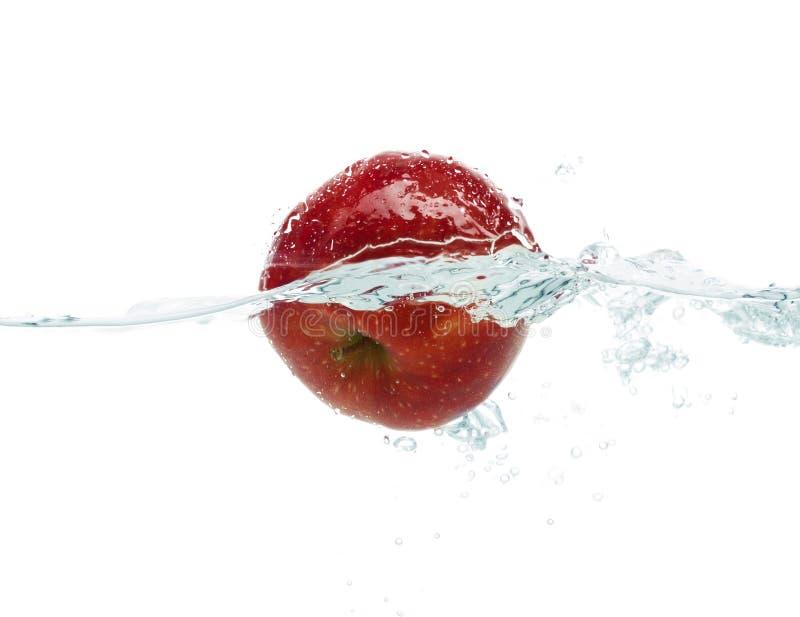 Apple que cae o que sumerge en agua con el chapoteo imagen de archivo