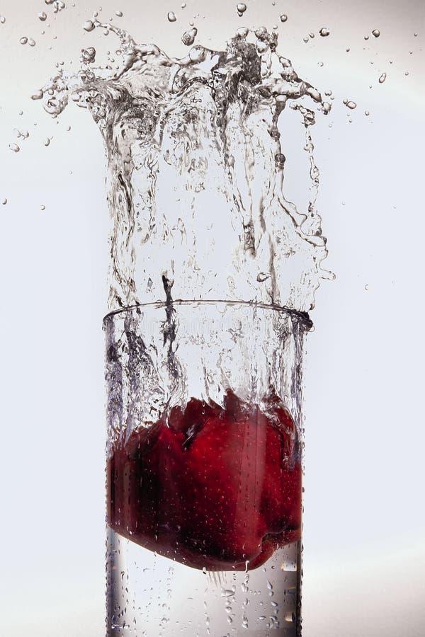 Apple que espirra no vidro da água imagens de stock royalty free