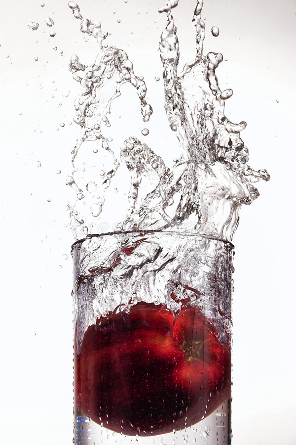 Apple que espirra no vidro da água fotos de stock