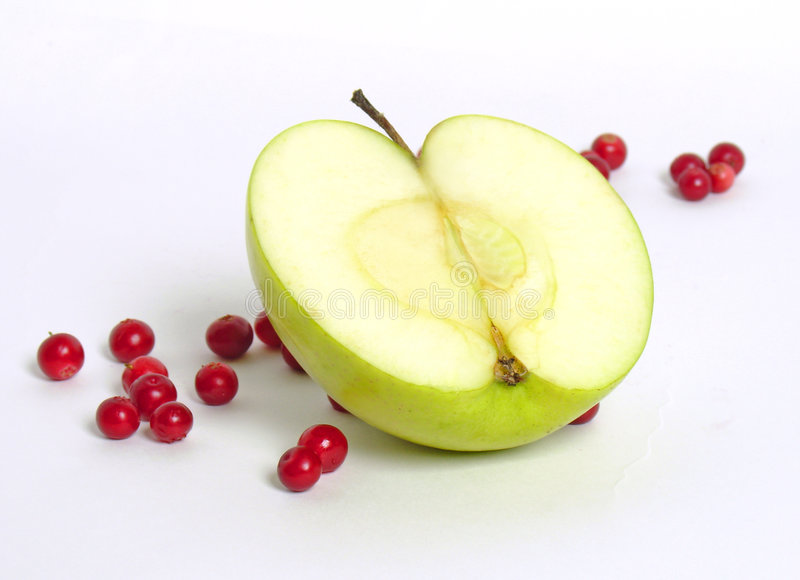 Apple with red bilberries. Half of a green apple with red bilberries on white background stock photography