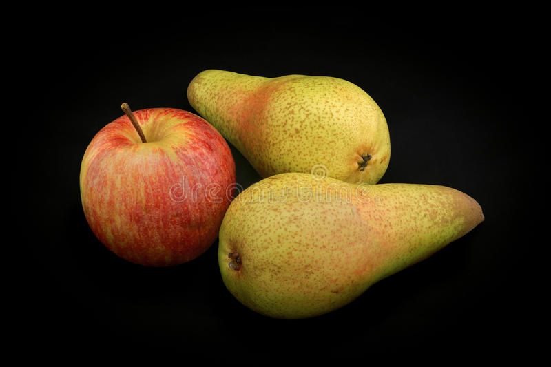Apple of red color and two pears of yellow color on a black back stock photo