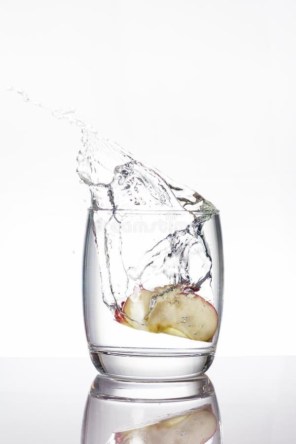 Apple remenda a gota em um vidro da água, faz o espirro da água fotografia de stock