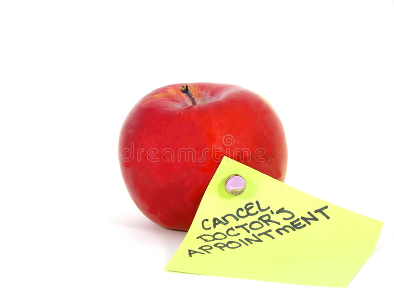 Apple and Reminder. Macro photo of red apple and cancellation reminder on green note with white background royalty free stock photos