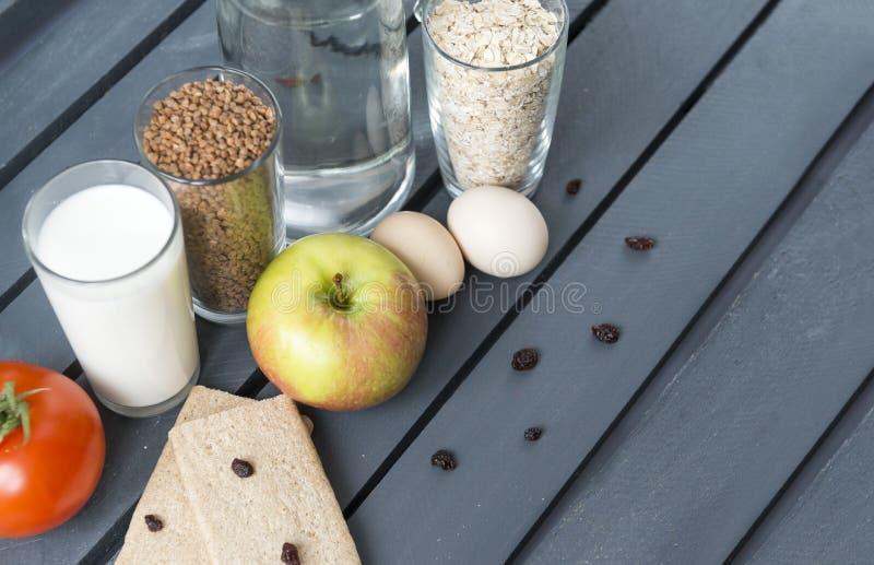 Apple, 2 rohe Hühnereien, Laibe, Rosinen, Tomate, Glas Milch, Buchweizen in einem Glas, Haferflocken in einem Glas, Wasser in ei stockbild