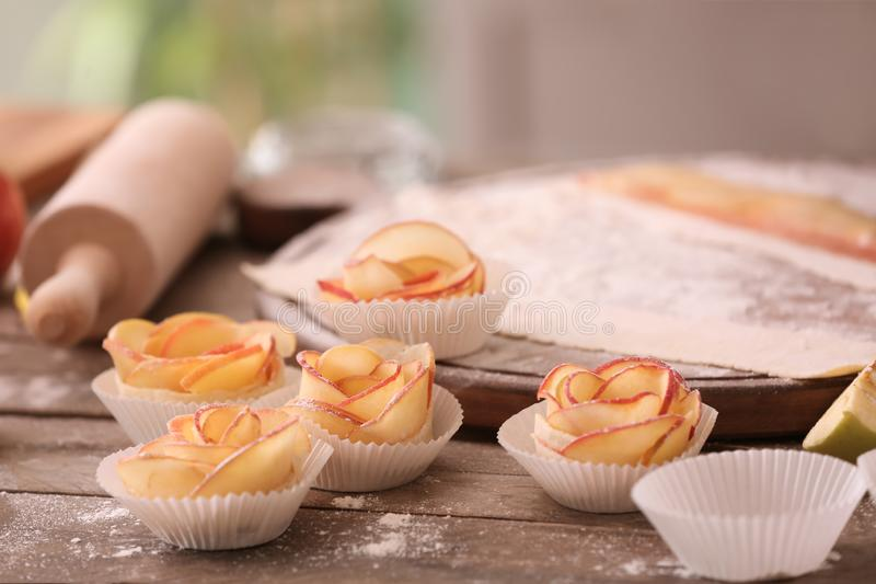 Apple roses from puff pastry on kitchen table stock photo