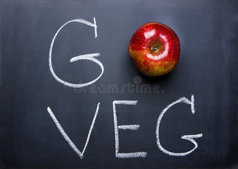 Apple rosso sulla lavagna nera passa l'iscrizione va Veg Dieta sana Superfood di concetto vegetariano del vegano immagini stock libere da diritti