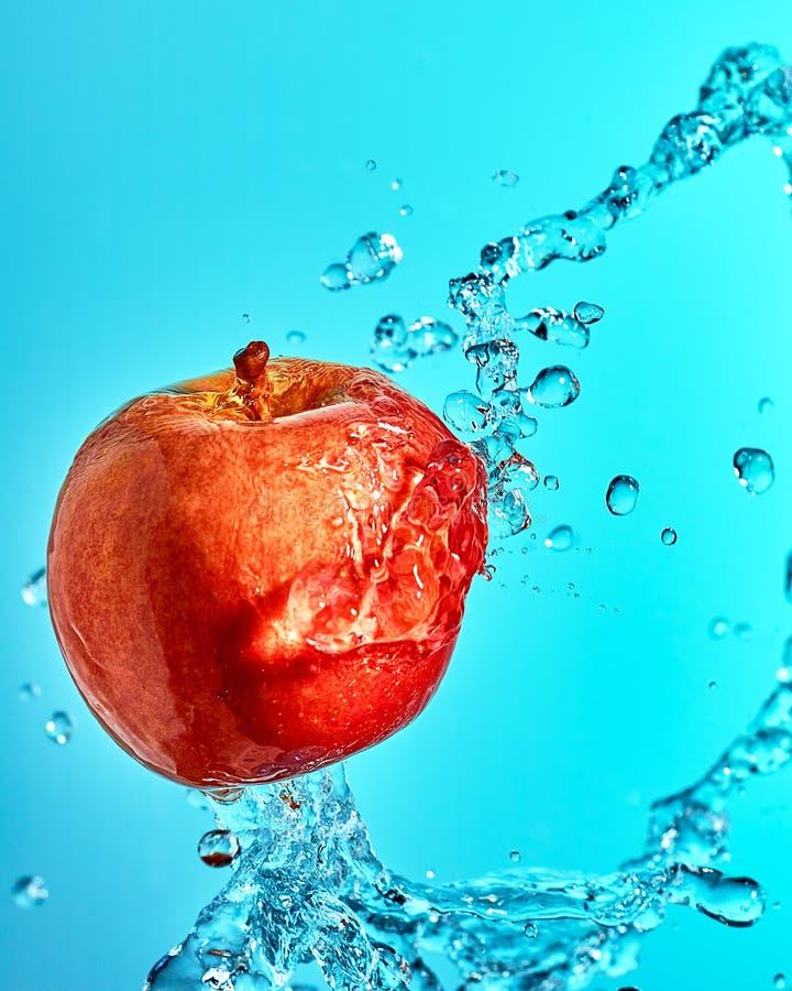 Apple rouge dans le jet volant de l'eau photos stock