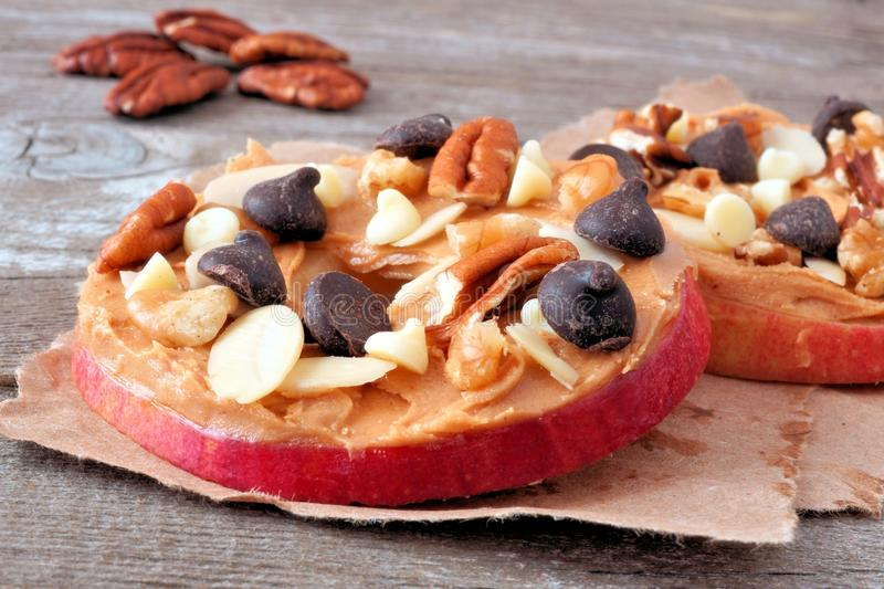 Apple rounds close up with peanut butter, chocolate and nuts stock photo