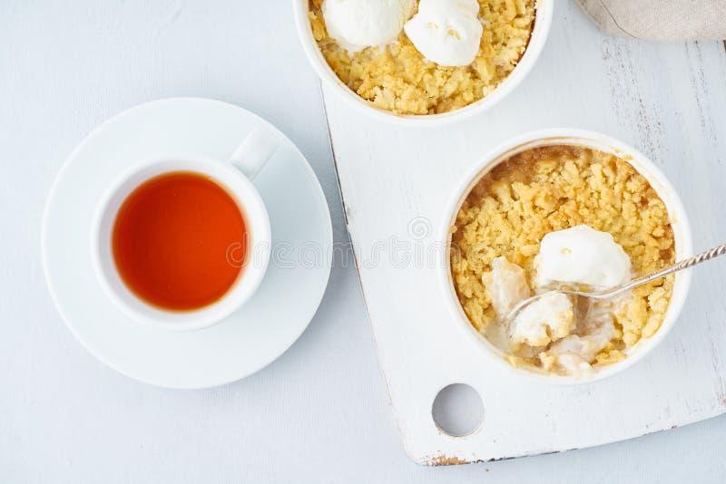 Apple rozdrobni z lody, streusel Ranku śniadanie z herbatą na świetle - szarość stół Odg?rny widok, zamyka up fotografia royalty free