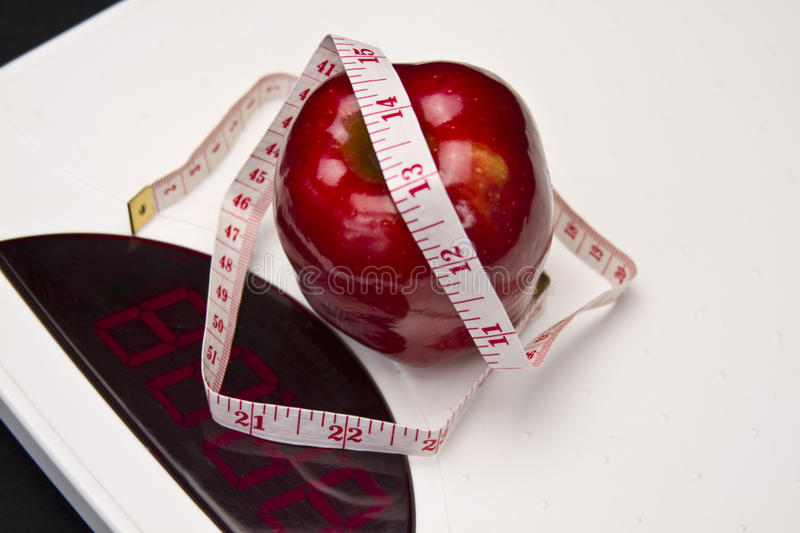 Apple on Scales. Concept of losing weight and living helthy wtih apple, tape measure on weighing scales royalty free stock images