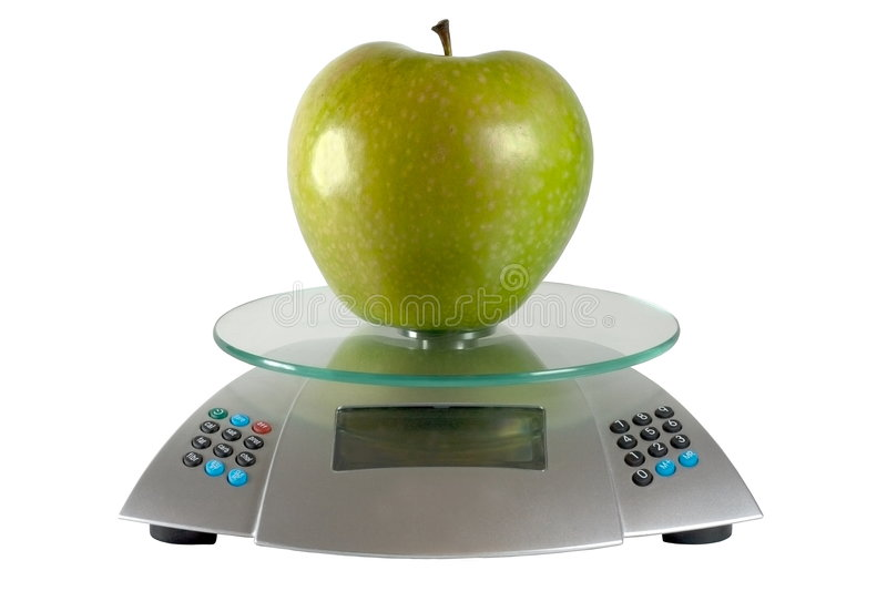 Apple and scales. Green apple on glass scales royalty free stock image