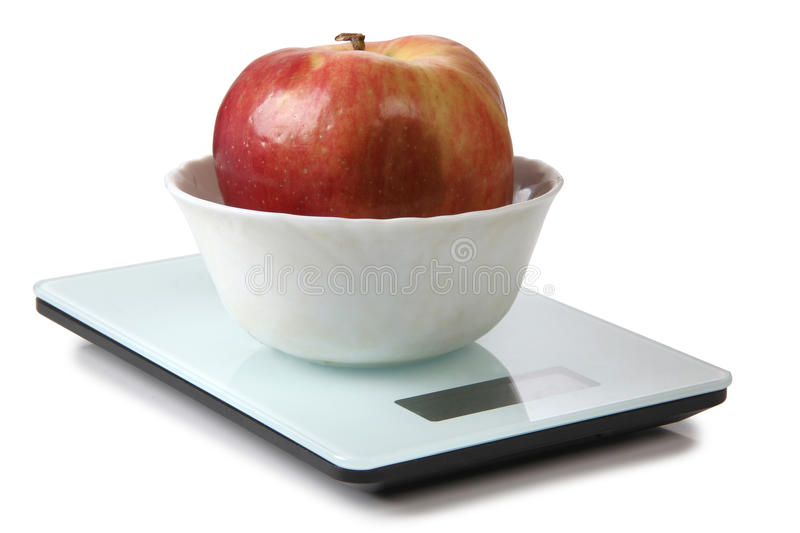 Apple on scales. Big red apple on electronic scales stock image