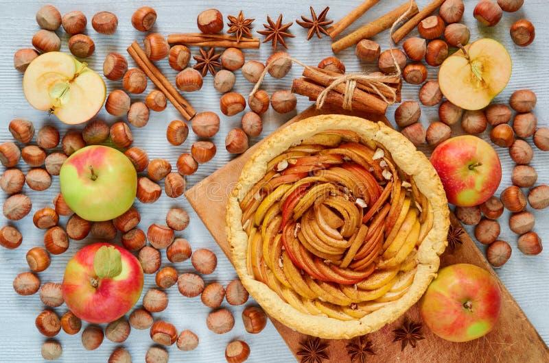 Apple scherp op de houten raad verfraaide met verse appelen, hazelnoten en kruiden - anijsplantsterren en kaneel op de grijze lij stock foto