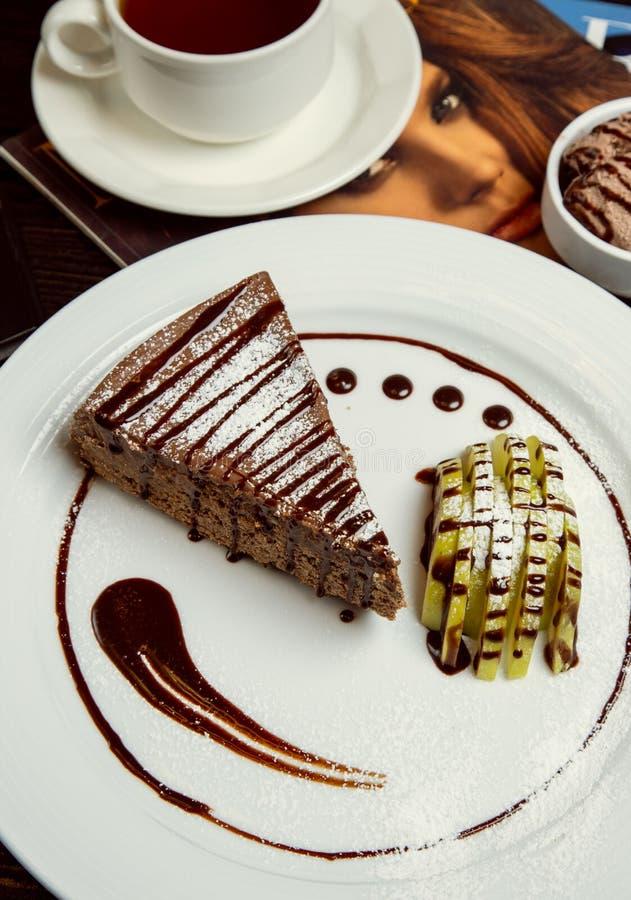 Apple-Schokoladenkakaotorten-Kuchenscheibe mit Apfelscheiben und Schokoladensoße stockbilder